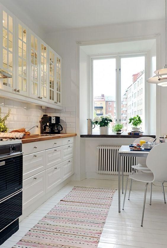 une belle cuisine nordique blanche avec des comptoirs de boucherie et des chaises modernes ainsi qu'une grande fenêtre avec beaucoup de lumière naturelle