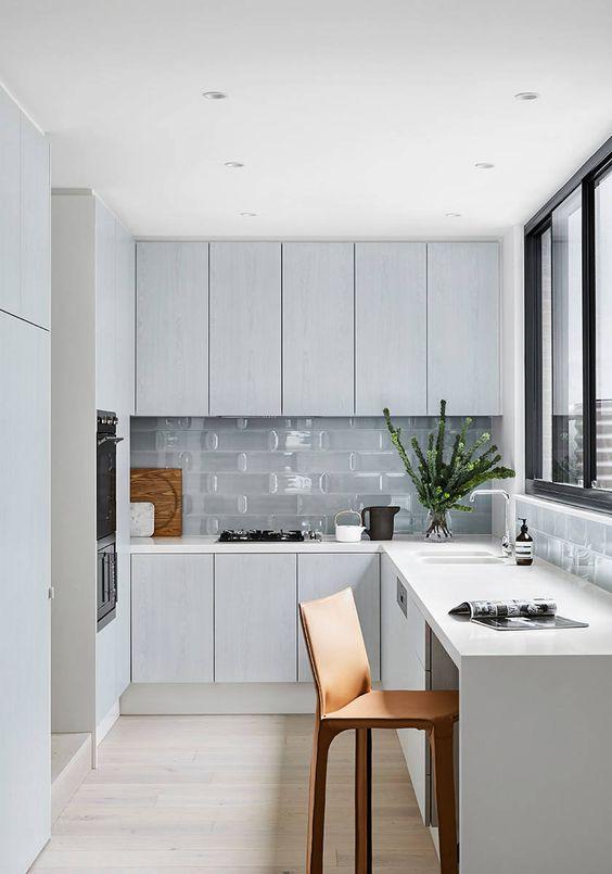 une cuisine nordique minimaliste en forme de L avec des carreaux de verre et une fenêtre avec vue est une belle idée