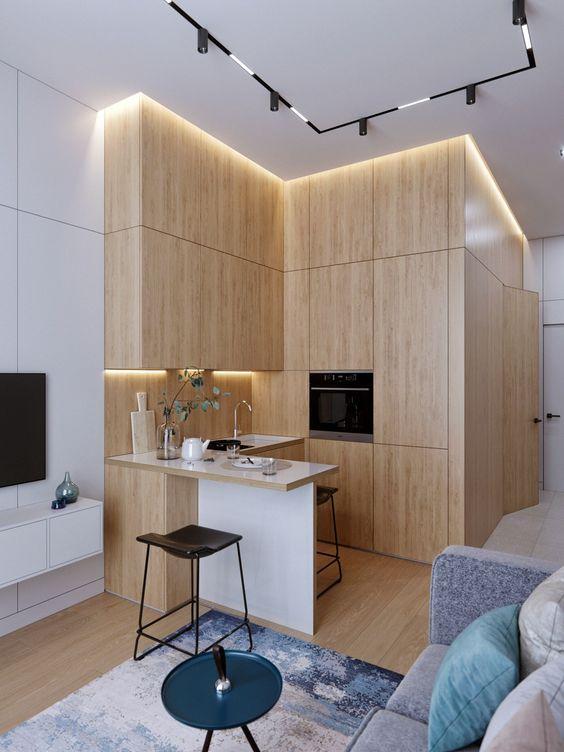une cuisine en forme de L en bois blond minimaliste avec des lumières intégrées et un petit îlot de cuisine est super cool