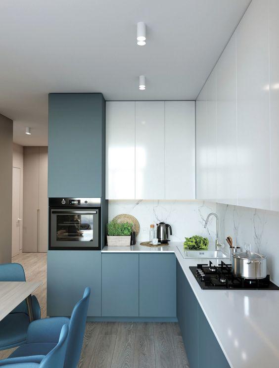 une cuisine minimaliste bleu et blanc avec un dosseret en pierre blanche et des comptoirs blancs est tout chic