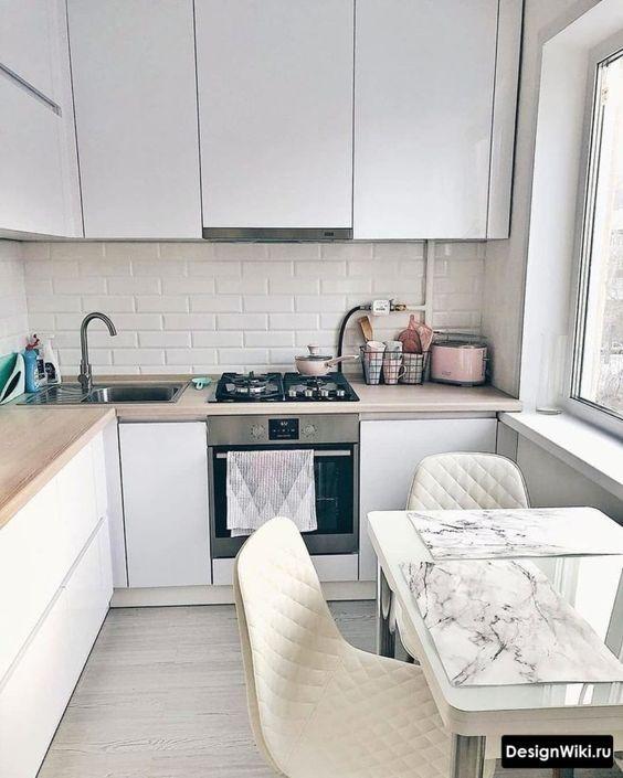 une cuisine minimaliste en forme de L avec des armoires élégantes et des comptoirs de boucherie ainsi qu'une petite zone de repas