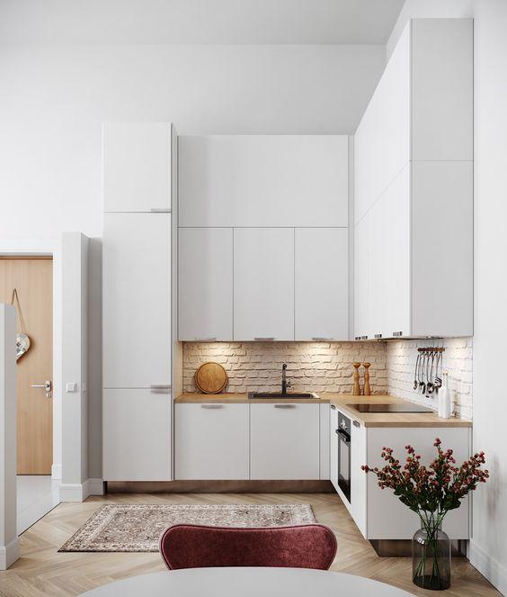 une cuisine en forme de L blanc minimaliste avec un dosseret en brique, des comptoirs en bloc de boucherie et des lumières intégrées