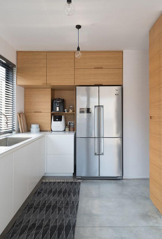 une cuisine bicolore minimaliste avec des armoires élégantes, des comptoirs en pierre blanche et un tapis imprimé est très élégante