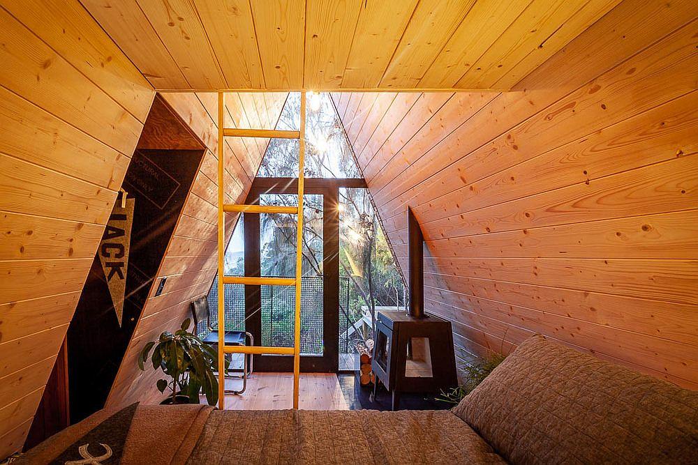 Cheminée couplée à des lits superposés et des coins confortables à l'intérieur de la cabane dans les arbres moderne