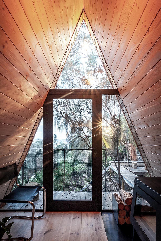 Cabane dans les arbres à ossature A avec des murs en verre et des fenêtres qui amènent l'extérieur à l'intérieur