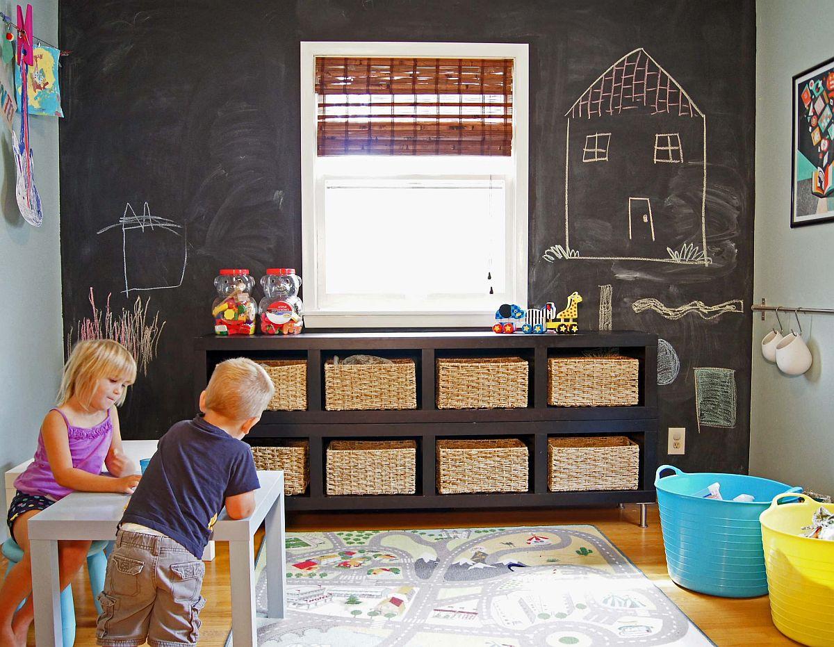 Salle de jeux amusante avec de petits paniers de rangement pour les jouets et un mur de tableau en toile de fond