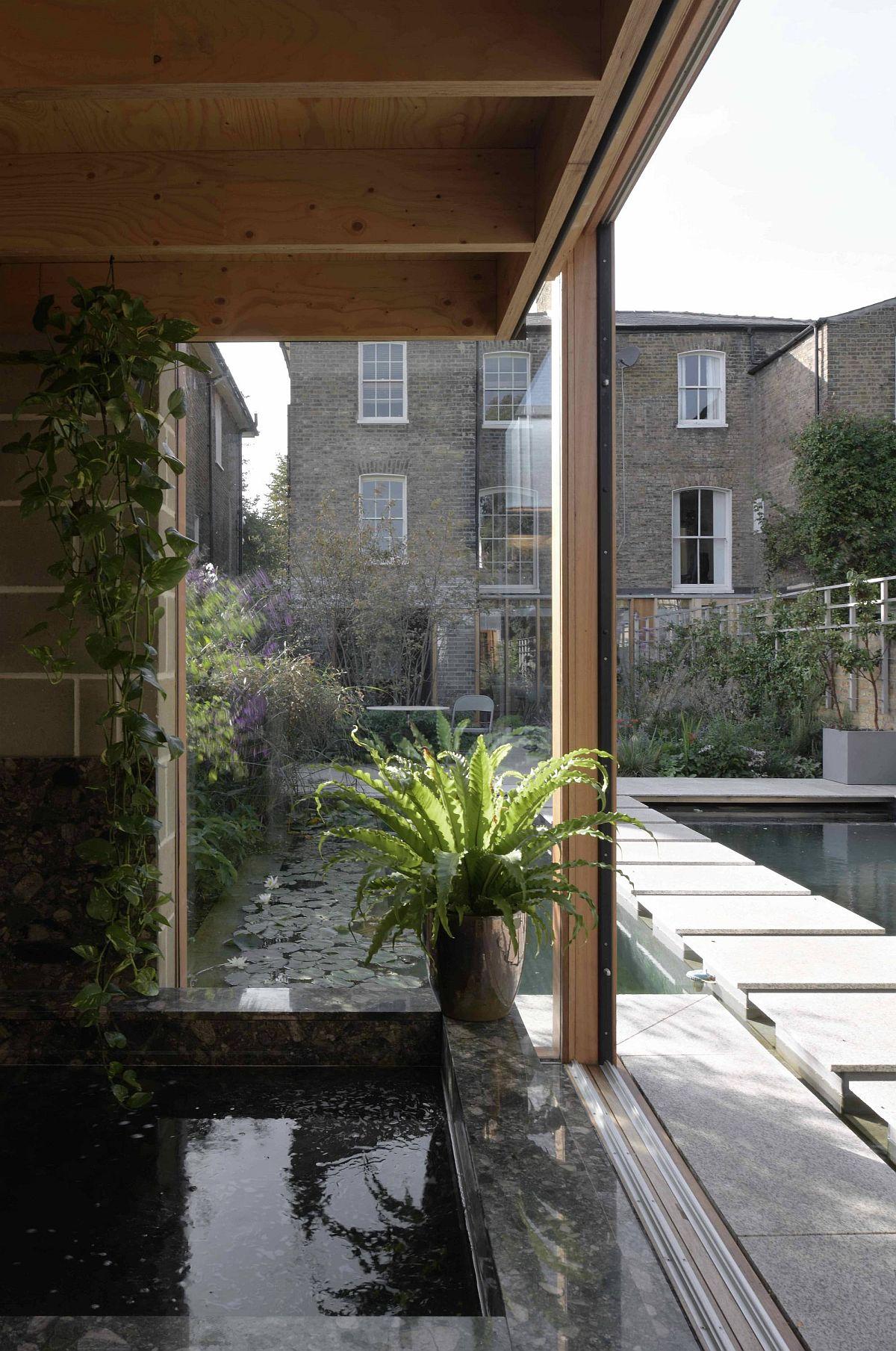 Les pièces d'eau et la verdure deviennent une partie naturelle de la charmante salle de jardin