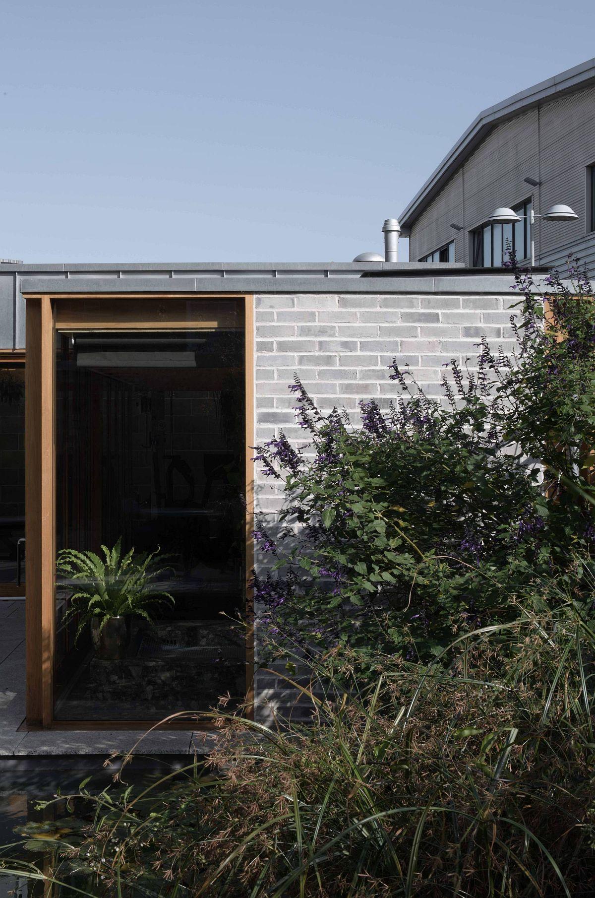 Les murs en parpaings exposés, le bois et le verre forment la belle évasion de la cour arrière