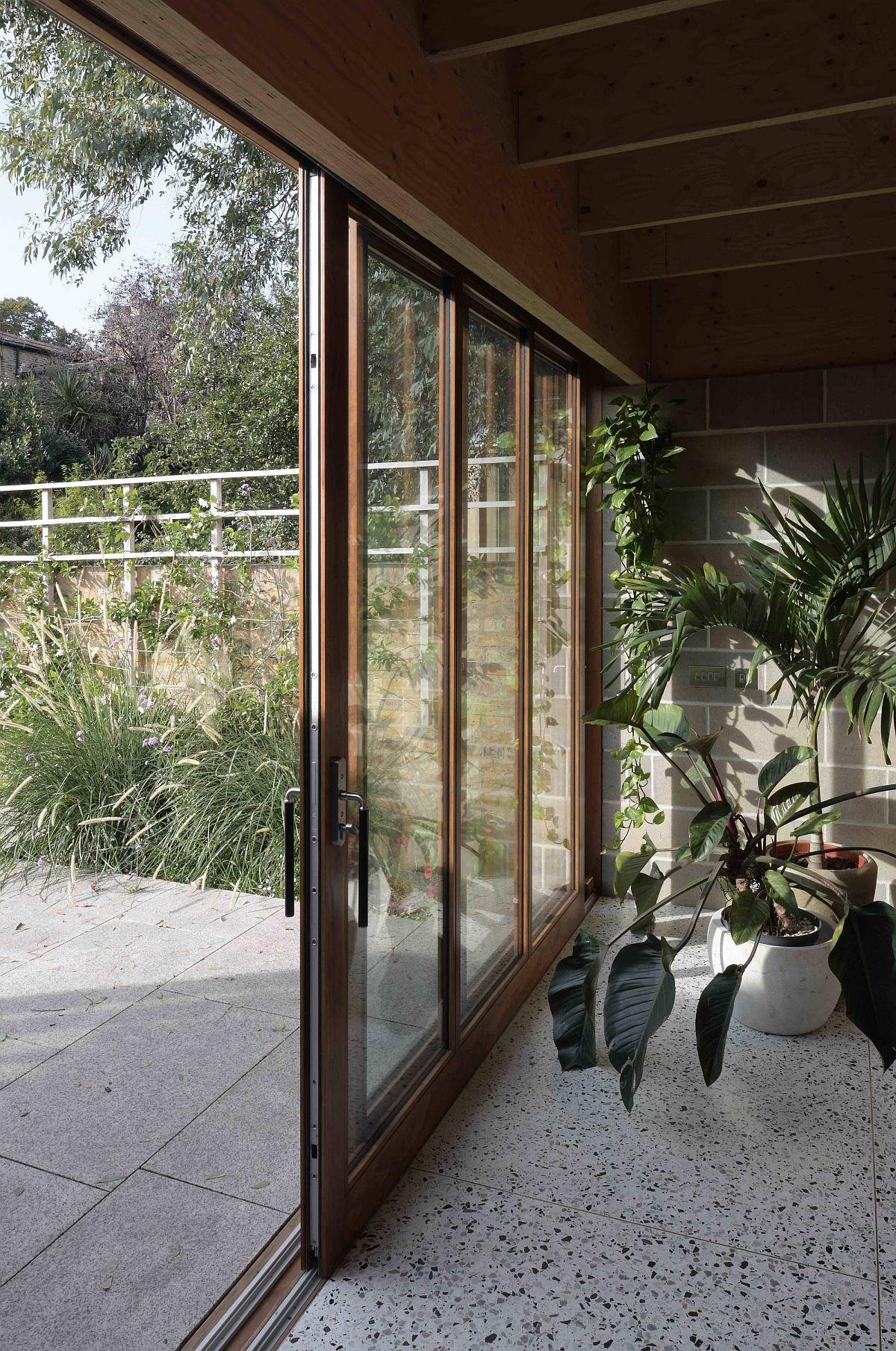 Les portes coulissantes en verre relient l'intérieur avec le jardin extérieur