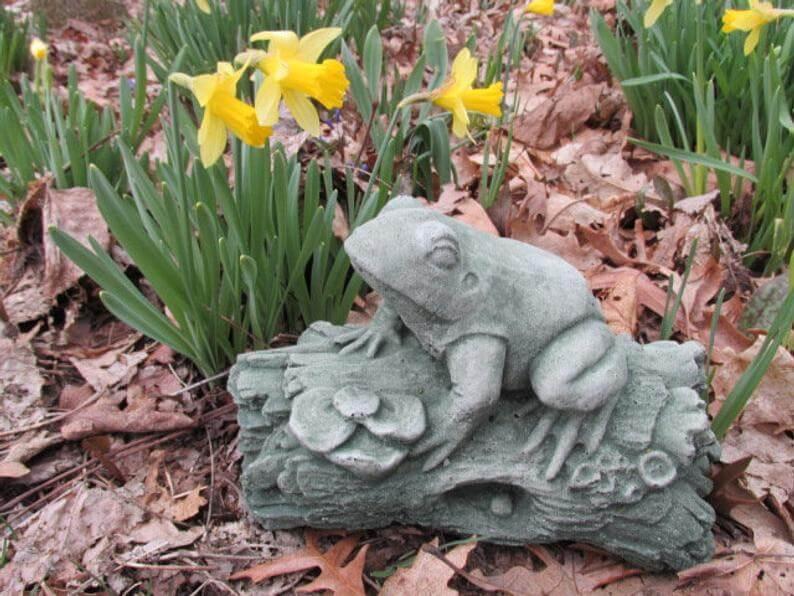 Grenouille gambadante sur une sculpture de jardin en rondins