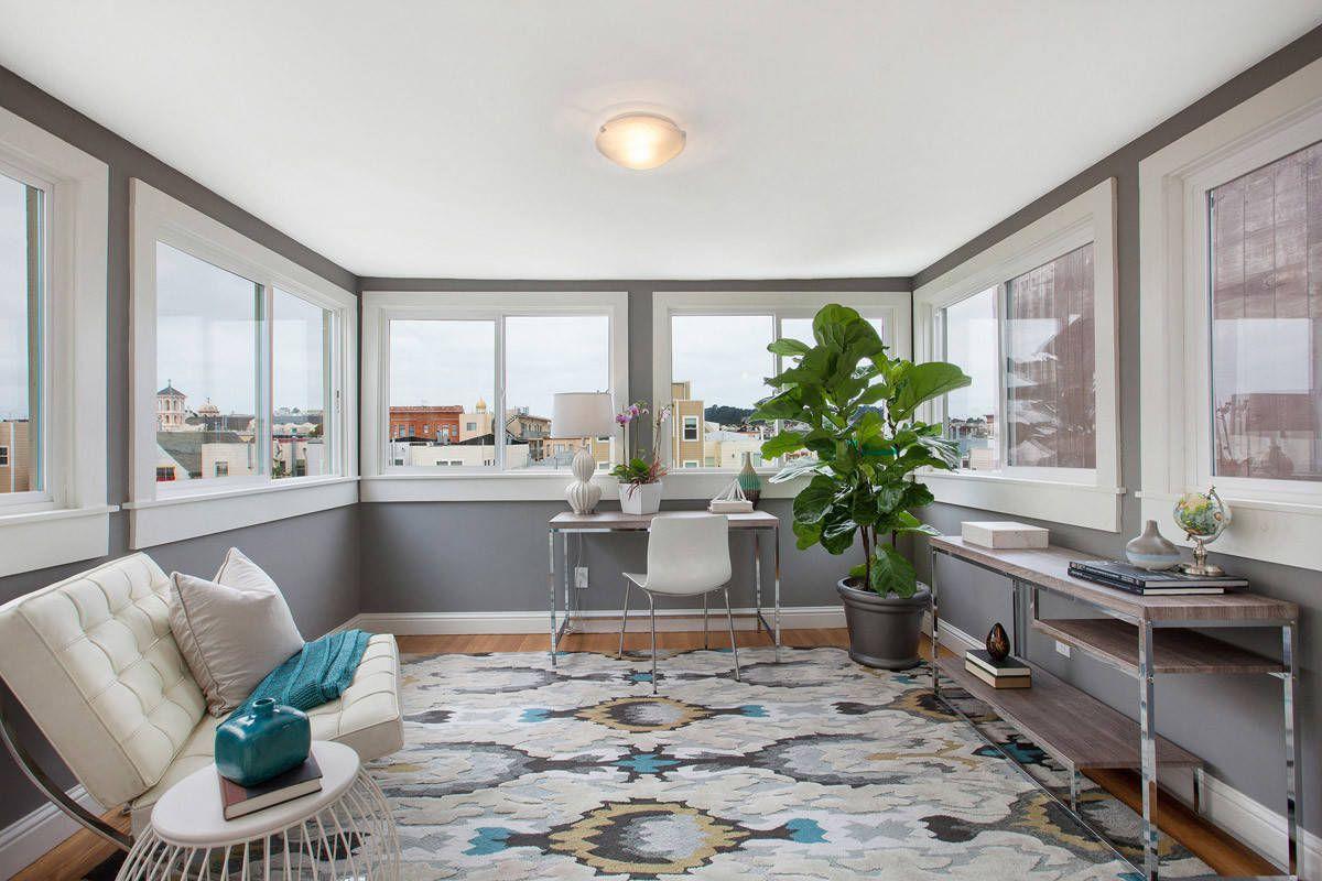 Bureau à domicile de style transitionnel rempli de lumière avec une grande plante d'intérieur dans le coin et des murs gris