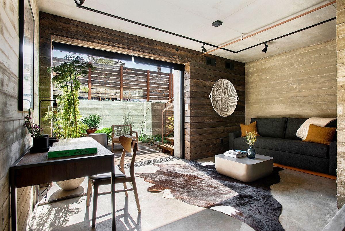Bureau à domicile de style industriel où la verdure extérieure devient une partie de l'intérieur