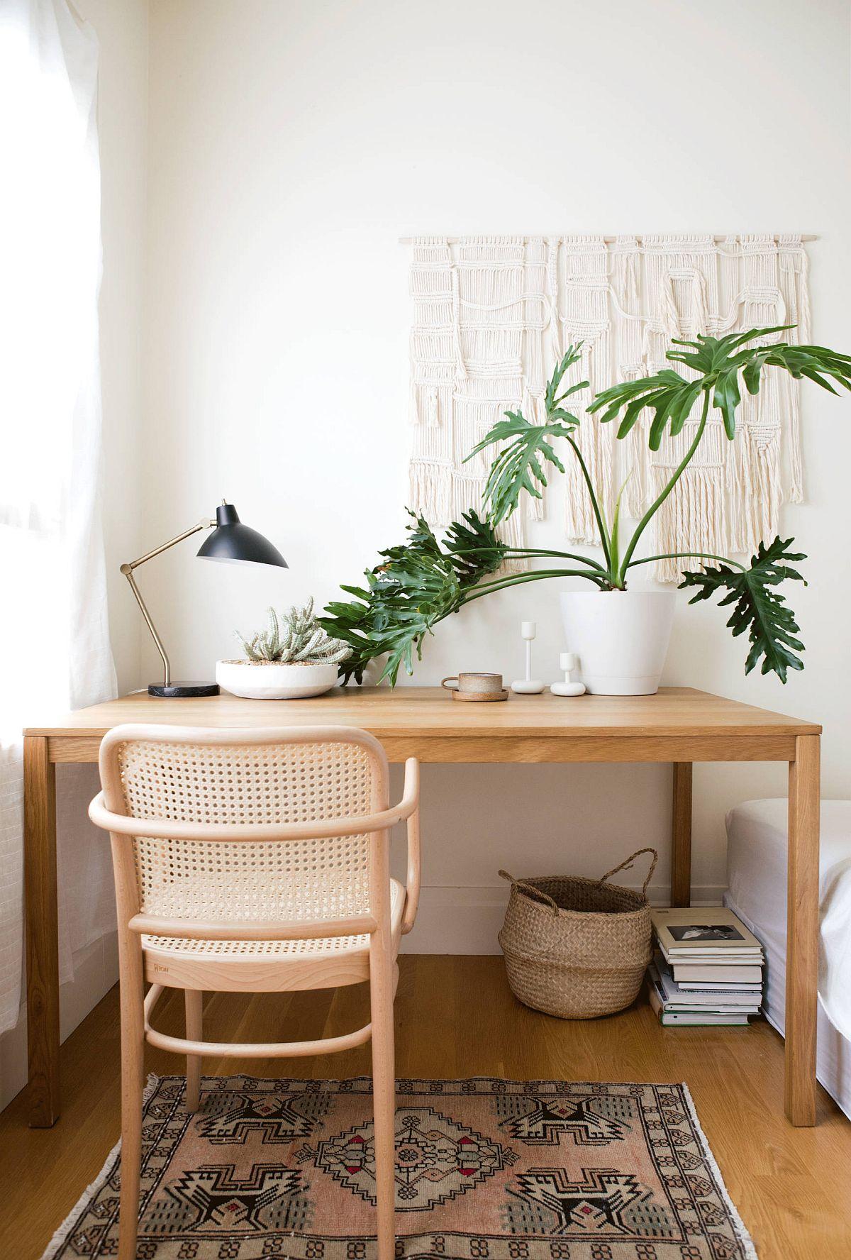 Bureau à domicile de style scandinave en bois et blanc avec une touche de vert apportée par les plantes d'intérieur