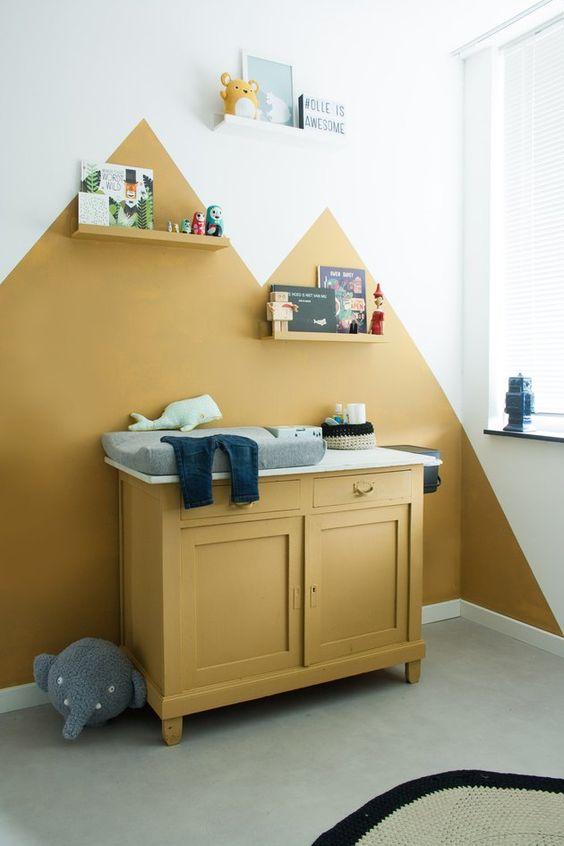 une pépinière audacieuse avec des blocs de couleur moutarde sur le mur, une armoire à moutarde, des étagères, des jouets et des œuvres d'art et des touches de gris