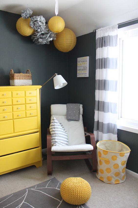 une chambre d'enfant noire, blanche et jaune avec des lampes en papier et des pompons, une commode jaune, une bascule, un panier et un pouf en tricot plus des rideaux à rayures