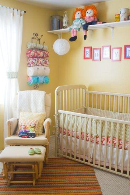 une pépinière jaune joyeuse avec des meubles vintage, une étagère avec des jouets, des textiles colorés et de la literie et une chaise confortable avec un repose-pieds