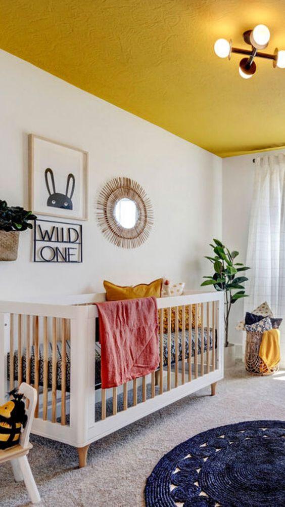 une chambre d'enfant lumineuse et amusante avec un plafond jaune, des draps jaunes, des tapis superposés, un berceau et un joli mur de galerie de style bohème