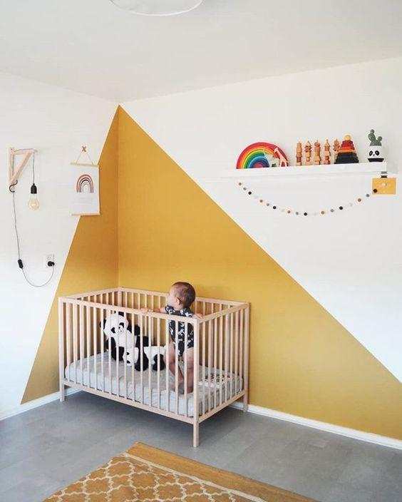 une chambre d'enfant moderne et lumineuse avec des blocs de couleur jaune sur le mur et un tapis jaune, un berceau neutre, une étagère avec des jouets et des affiches