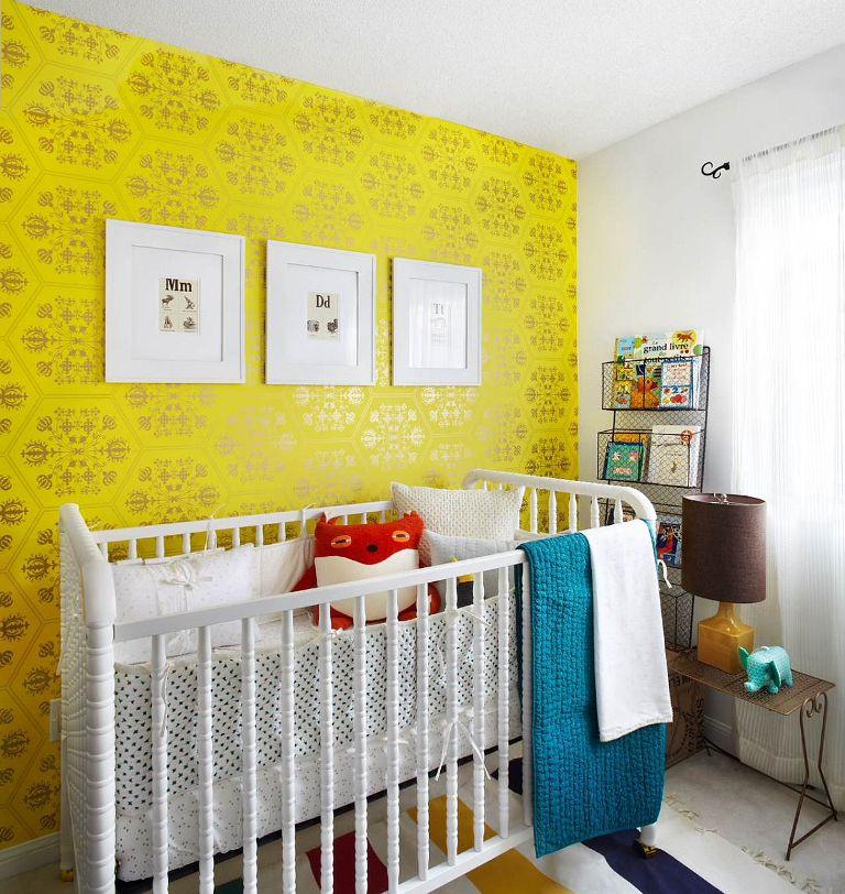 une chambre d'enfant colorée avec un mur de papier peint jaune vif, un berceau blanc, une étagère en fil de fer, des textiles et une literie colorés ainsi qu'un mur de galerie