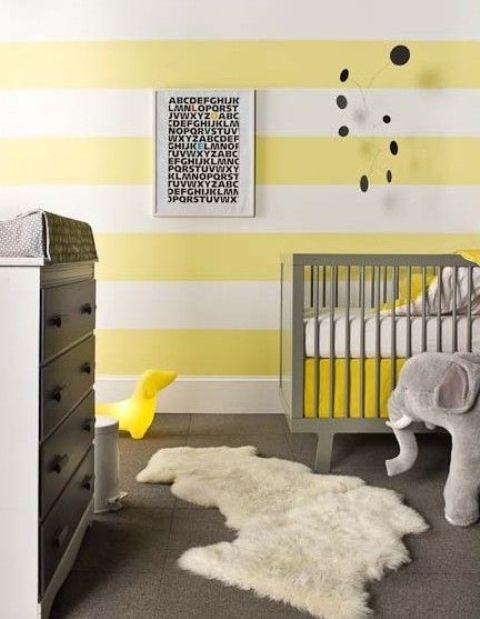 une chambre d'enfant lumineuse avec un mur rayé jaune et blanc, des meubles gris, un tapis en fausse fourrure, des jouets et une affiche