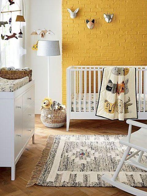 une pépinière joyeuse avec un mur de briques jaunes, des meubles blancs, un tapis imprimé, une taxidermie amusante et un mobile plus des paniers