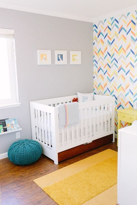 une pépinière colorée avec un mur géométrique lumineux, des meubles blancs et jaunes, un tapis jaune, un pouf bleu et un mur de galerie