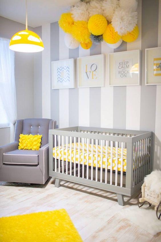 une jolie chambre d'enfant grise, blanche et jaune avec un mur d'accent rayé, des meubles gris, beaucoup de pompons en papier et une suspension jaune