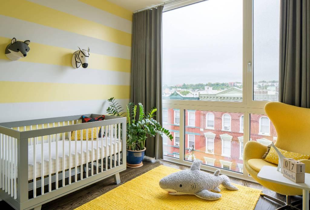 une pépinière amusante avec un mur jaune à rayures, un tapis et une chaise, des meubles gris et blancs et une fausse taxidermie