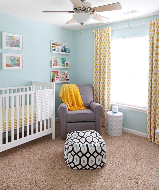 une chambre d'enfant confortable avec des murs bleu clair, un berceau blanc, une chaise grise, des draps jaunes et des rebords avec des livres et des œuvres d'art