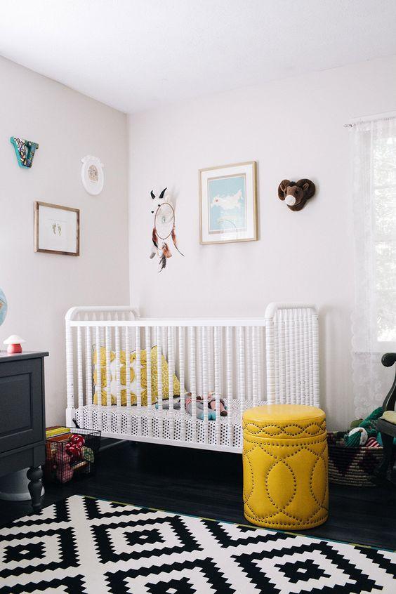 une chambre d'enfant contrastée en noir et blanc, avec des meubles en noir et blanc, des touches jaunes et un joli mur de galerie