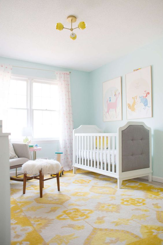 une chambre d'enfant colorée avec des murs bleu clair, des meubles neutres, un mur de galerie coloré, un tapis et des rideaux imprimés ainsi qu'un lustre jaune