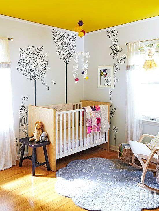 une pépinière fantaisiste avec un plafond jaune, des meubles simples, des murs peints, un tapis bleu, des textiles audacieux et des jouets