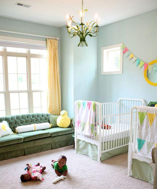 une chambre d'enfant partagée avec des murs bleu clair, un canapé vert, des berceaux blancs, une bannière et une literie colorées, des touches jaunes audacieuses et un lustre floral