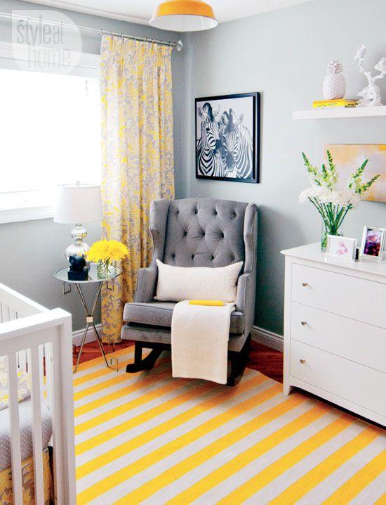 une petite chambre d'enfant aux murs gris, des meubles blancs et gris, une commode, une étagère ouverte, un tapis et des rideaux imprimés, une suspension jaune