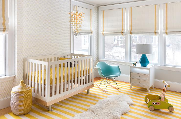 une chambre d'enfant aérée avec des murs blancs, un tapis rayé jaune, un berceau avec une literie jaune, des jouets et des stores romains à rayures jaunes