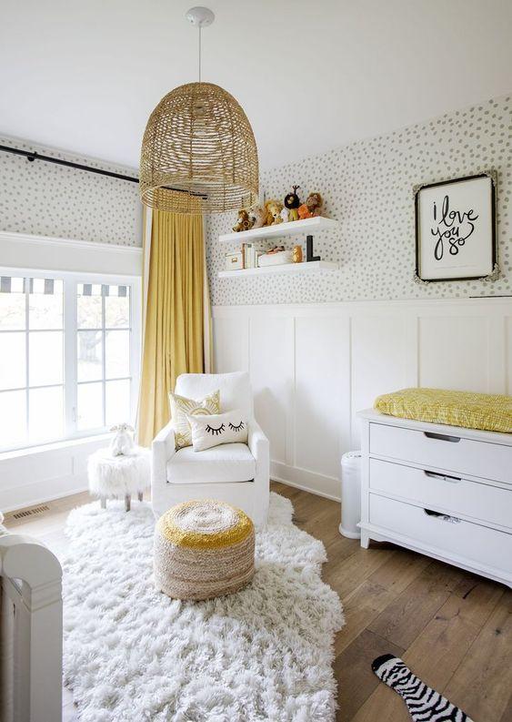 une chambre d'enfant aérée et amusante avec du papier peint à pois, des meubles blancs, une lampe en osier et des touches jaunes - des draps et un pouf