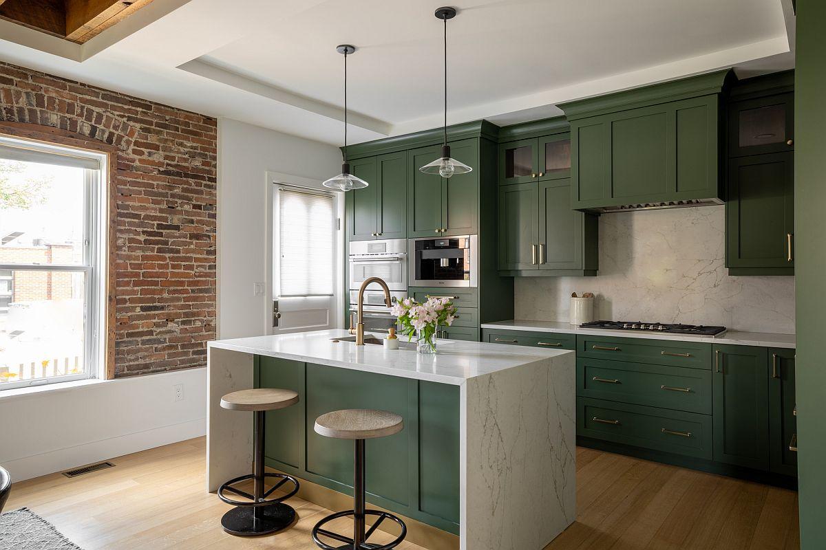 Les cuisines vert foncé exquises ajoutent de la couleur à cette cuisine industrielle moderne avec une section de mur en briques apparentes