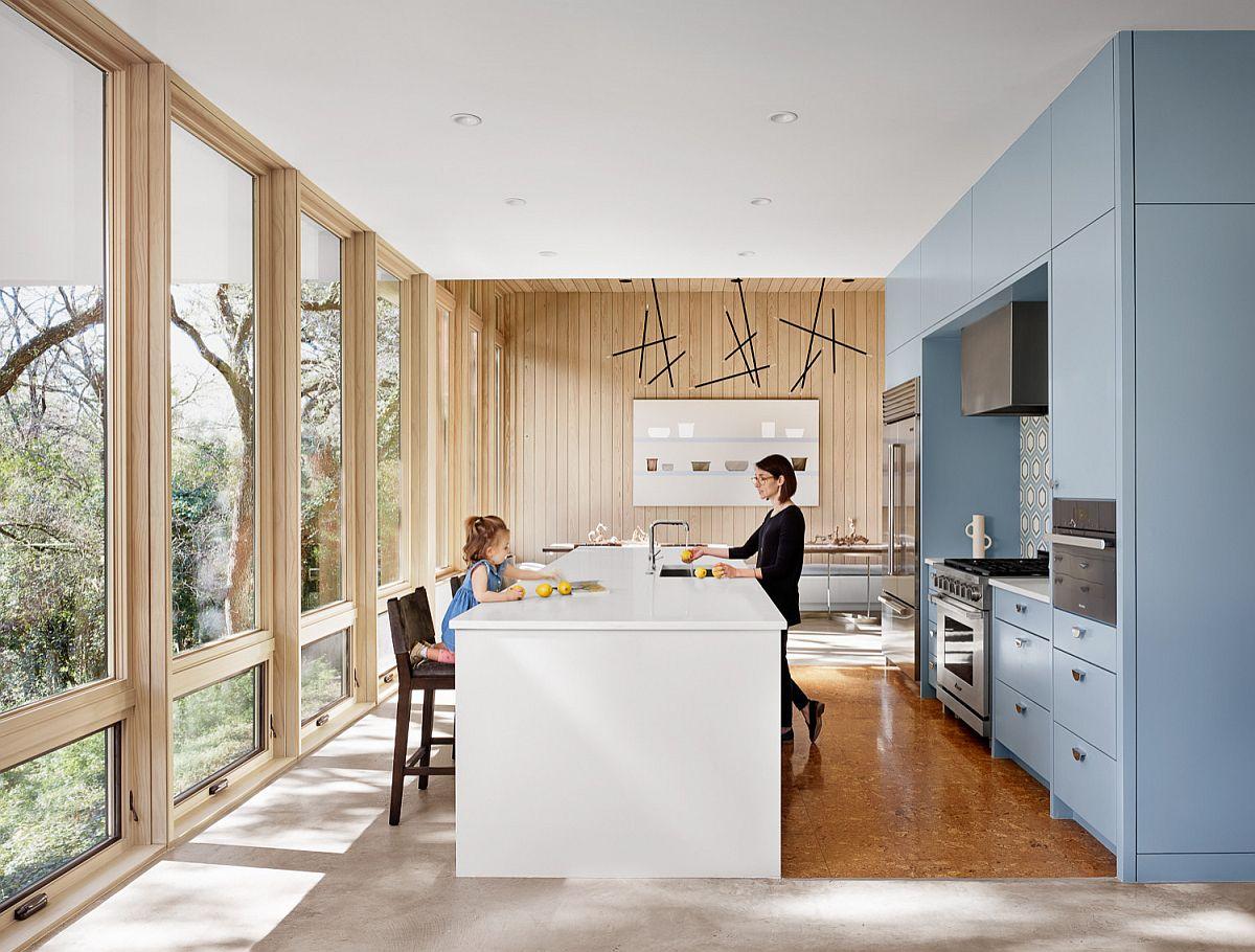 Cuisine moderne du milieu du siècle avec des murs en verre, des armoires bleues et un îlot central intelligent