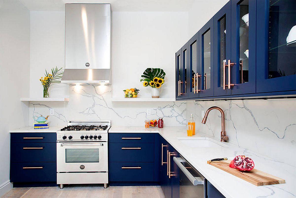Cuisine contemporaine en forme de I avec armoires bleu marine, dosseret en marbre blanc et luminaires en laiton