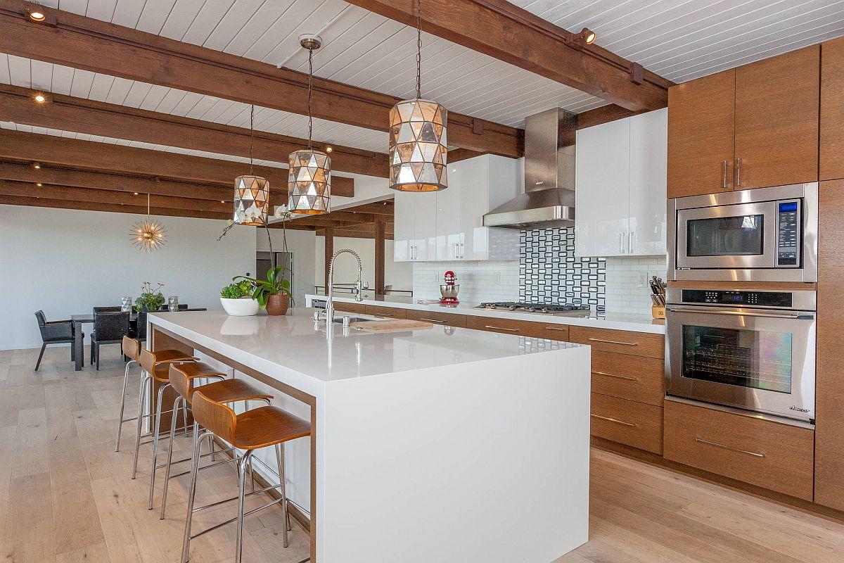 Armoires de cuisine en bois couplées à un îlot blanc dans la cuisine spacieuse du milieu du siècle