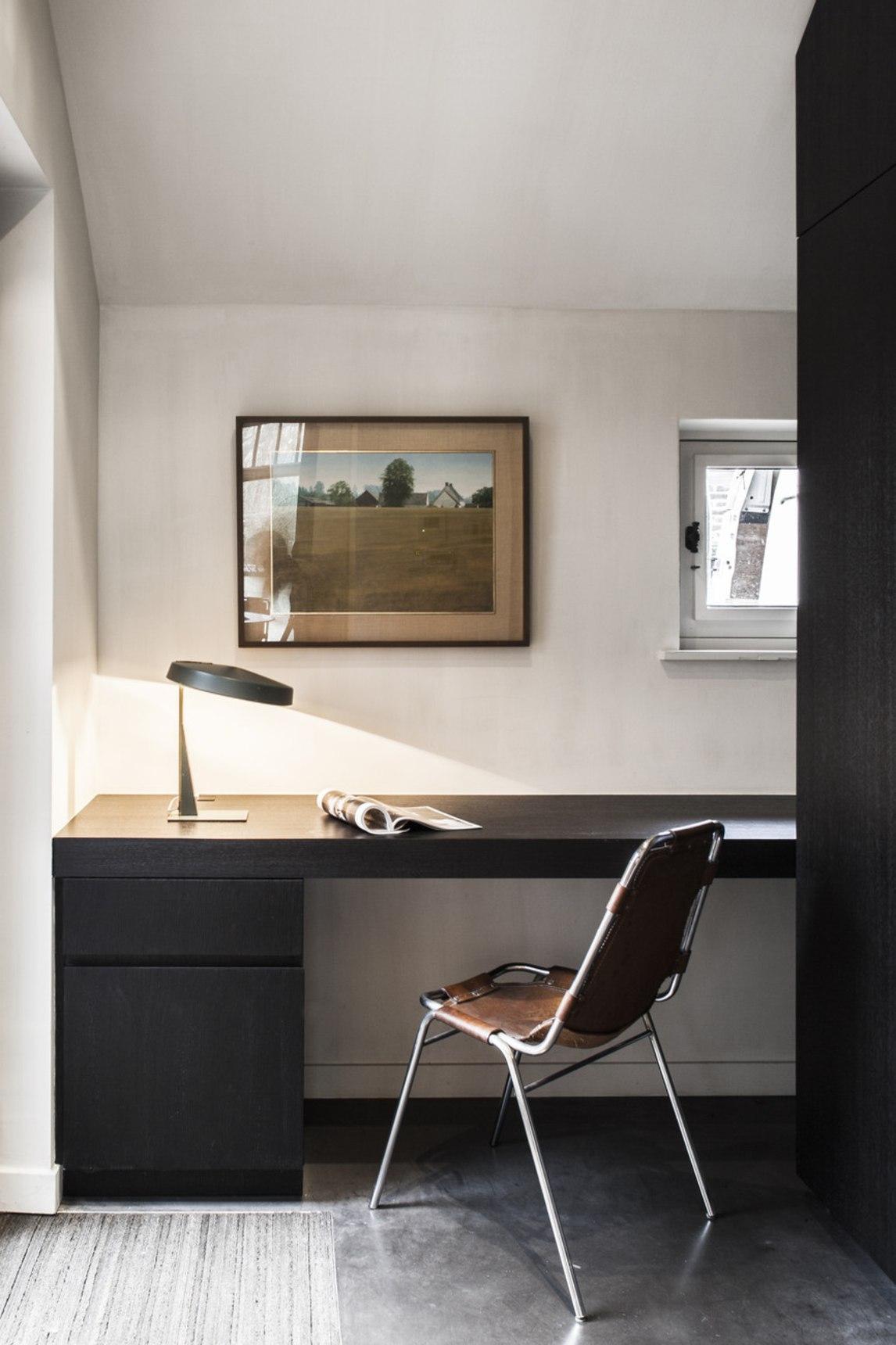L'espace de travail est très laconique, avec des meubles sombres et une chaise en cuir ainsi que des œuvres d'art