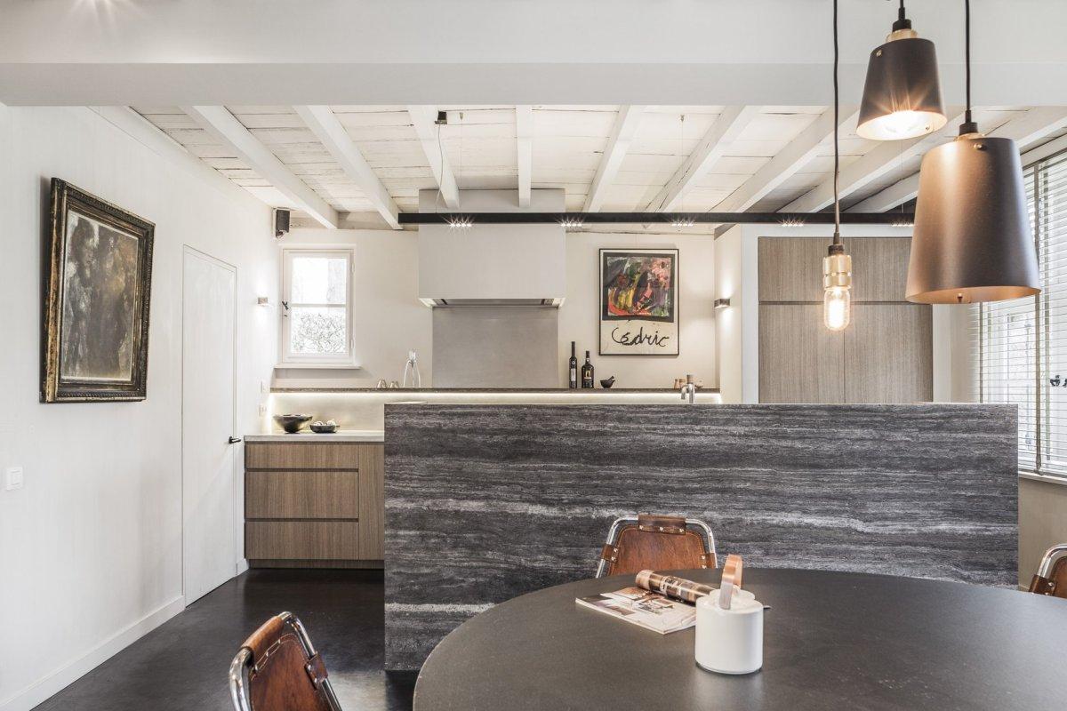 La cuisine est faite avec des armoires grises, un îlot de cuisine en pierre, des suspensions, l'espace salle à manger est ici