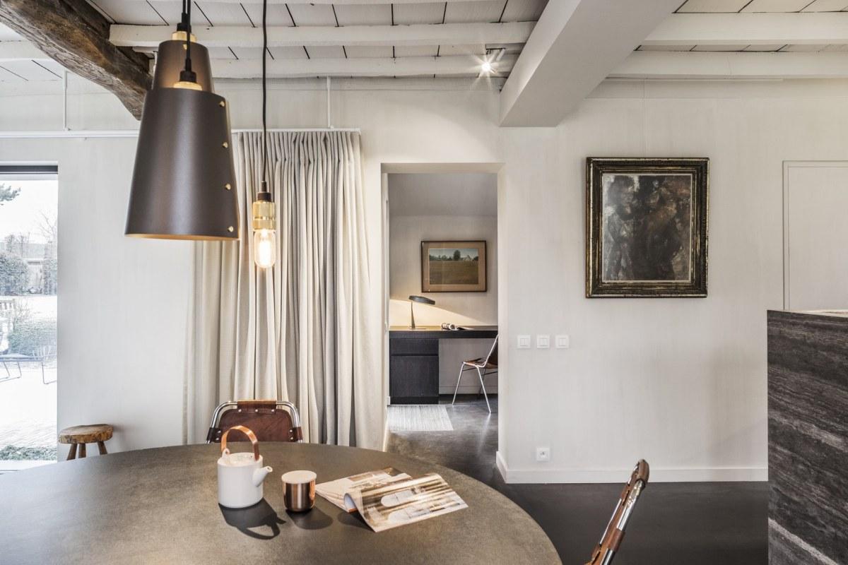 L'espace salle à manger est fait avec une table en béton, des chaises en cuir et en métal et des suspensions fraîches