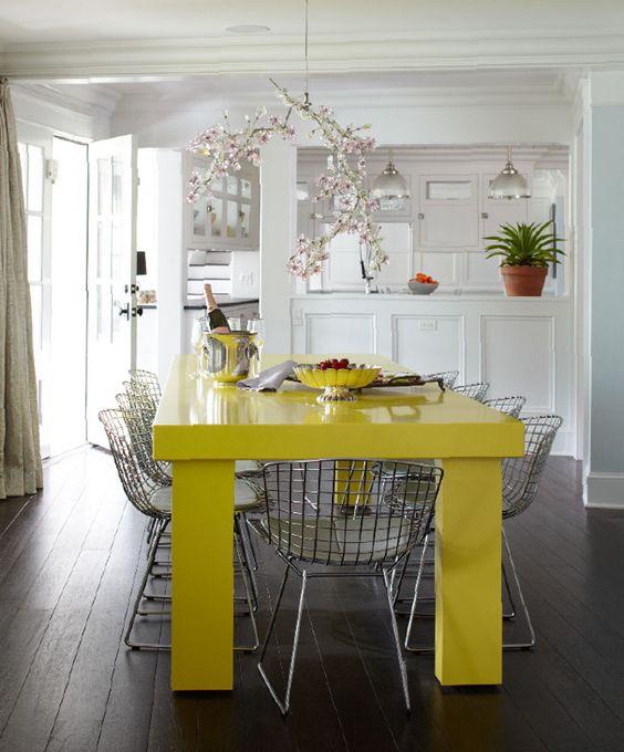 un espace salle à manger contemporain lumineux avec une table jaune fluo et des chaises en métal gris et un lustre fantaisiste en fleurs de cerisier
