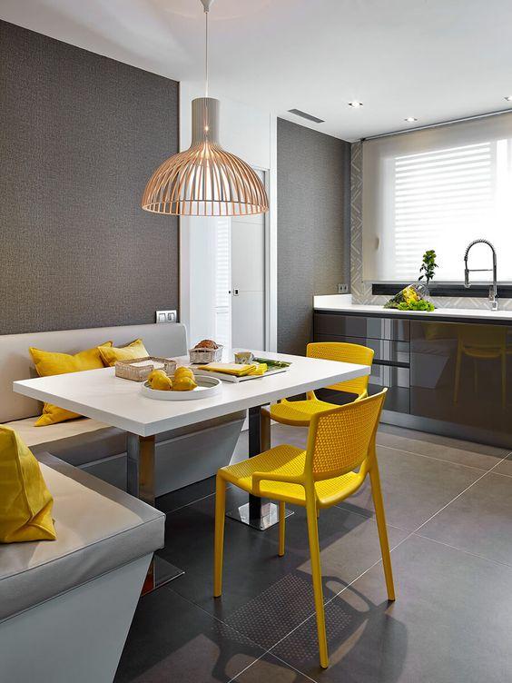 un coin repas moderne et audacieux dans la cuisine, avec un siège d'angle, une table, des chaises jaune vif et une jolie lampe