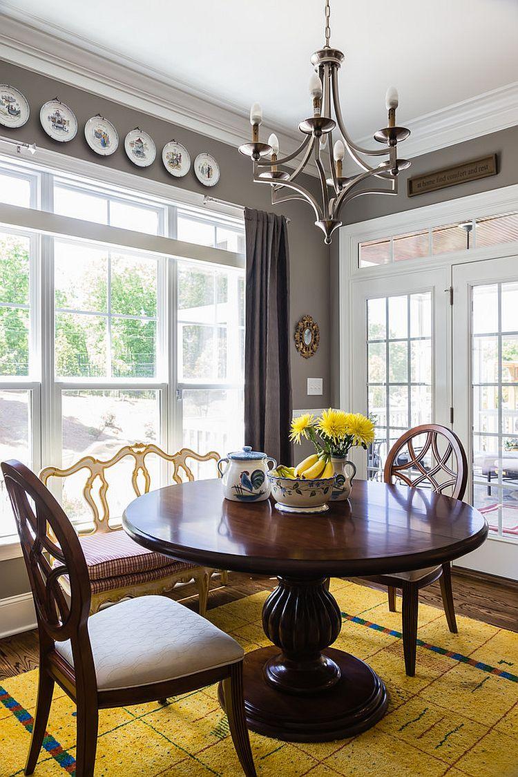 une salle à manger vintage audacieuse avec des murs gris, une grande fenêtre, une lourde table ronde et des chaises, des assiettes décoratives et un tapis jaune audacieux