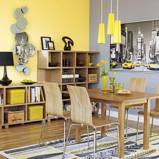 une salle à manger gris et jaune vif avec un mur d'accent gris et jaune, une unité de rangement ouverte, un ensemble de salle à manger élégant et des suspensions jaune citron