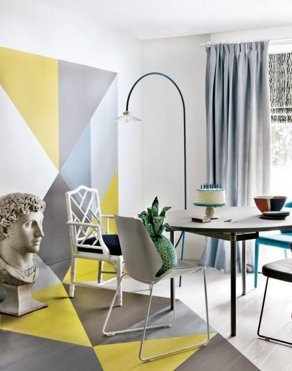une salle à manger lumineuse réalisée avec des blocs de couleurs géométriques, des chaises grises et blanches, une table moderne et un lampadaire accrocheur
