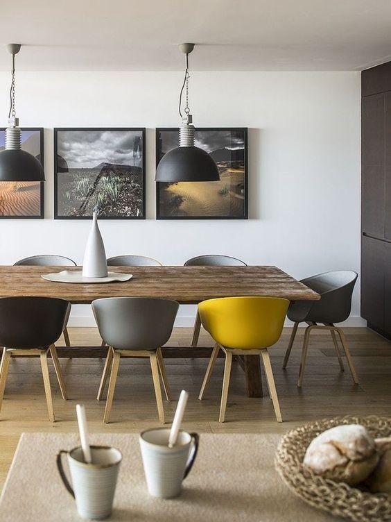 une salle à manger contemporaine grise et jaune, avec une table en bois, des chaises grises, noires et jaunes, des suspensions et un mur de galerie assorti