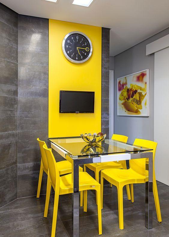 une salle à manger moderne et colorée avec une table à manger en verre, des chaises jaunes, un mur gris avec un effet de bloc de couleur réalisé avec un panneau jaune